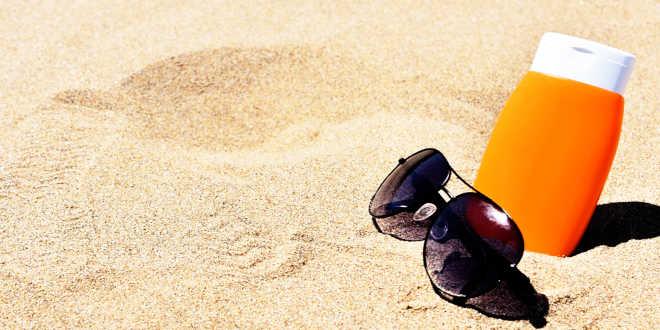 Crème solaire et lunettes de soleil à la plage
